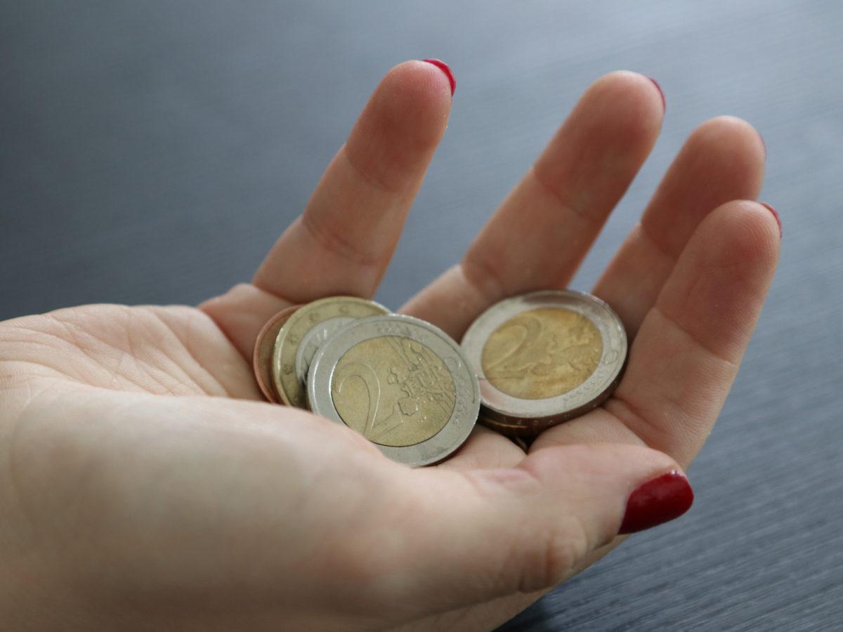 Weibliche Hand hält Euro-Münzen.