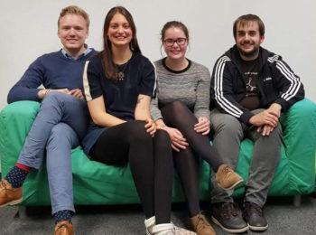 Vier Personen sitzen auf einem grünen Sofa.